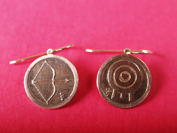 round sterling etched earrings with bow and arrow on the left and a target with a heart in the middle on the right displayed on a hot pink background closeup