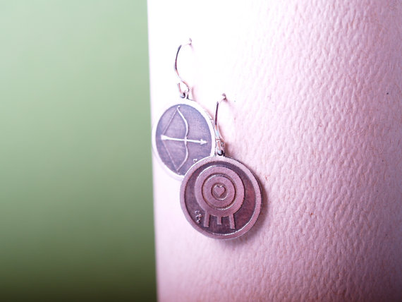 round sterling etched earrings with bow and arrow on the left and a target with a heart in the middle on the right
