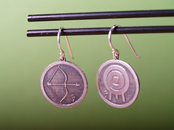 round sterling etched earrings with bow and arrow on the left and a target with a heart in the middle on the right displayed on a black bar wide shot