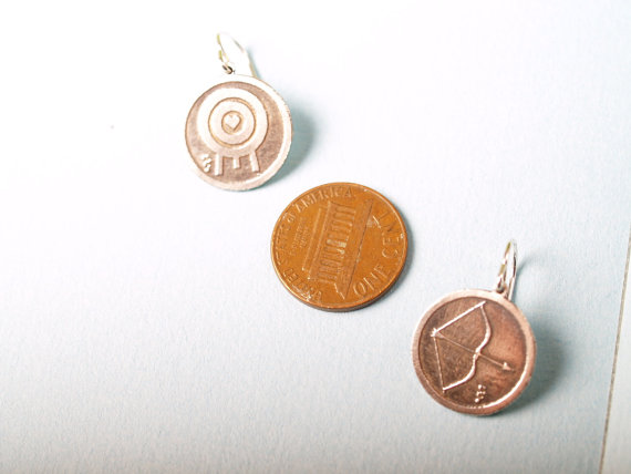 round sterling etched earrings with bow and arrow on the left and a target with a heart in the middle on the right - shown with a penny for scale