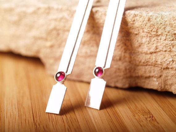 sterling handformed rectangular earrings with garnet cabochon against stone