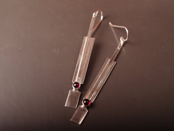 sterling handformed rectangular earrings with garnet cabochon laying flat on dark grey background