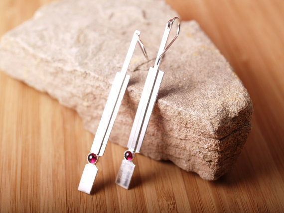 sterling handformed rectangular earrings with garnet cabochon leaned against a stone