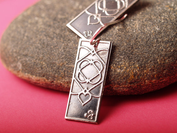 sterling silver rectangle earrings with celtic heart design french hooks hang long - displayed on rocky surface to show shiny nature or earrings