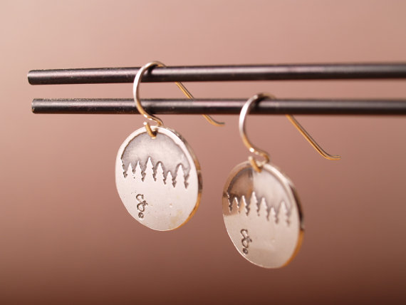 round sterling earrings etched with forest treeline hanging on black stand with copper backdrop