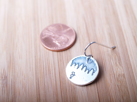 round sterling earrings etched with forest treeline with penny for scale