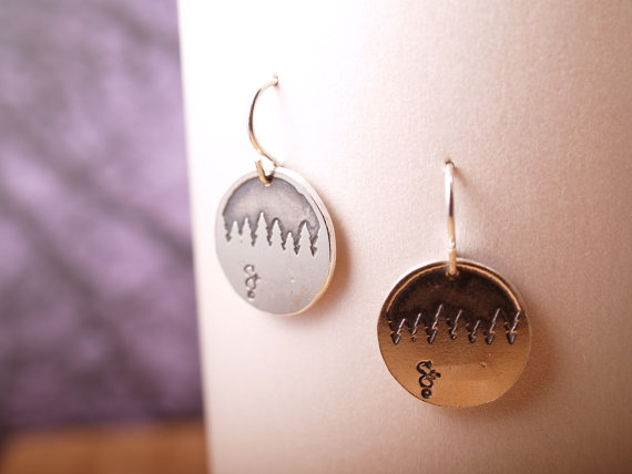 round sterling earrings etched with forest treeline hanging on white card