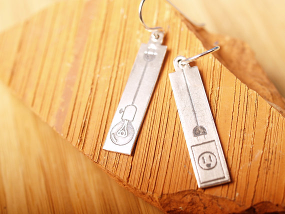 sterling rectangle etched earrings with french hooks right has a powersocket with a plug left has a lightbulb and a socket on terra cotta