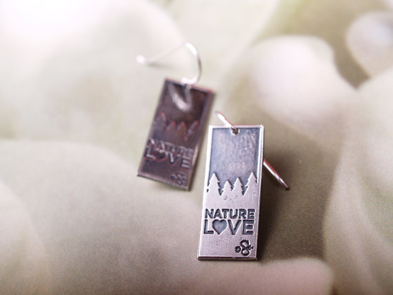 sterling rectangular etched earrings with french hooks - darker top treeline silhouette, Nature Love across the bottom - laying flat on floral background