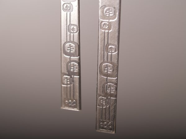 sterling etched long rectangle earrings with poppy design. French hook. Detail shot on grey background