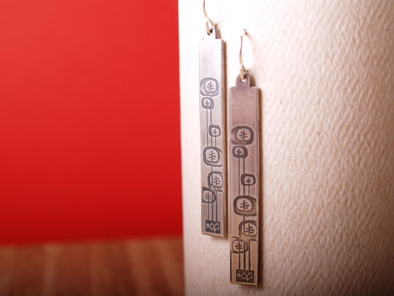 long rectangle sterling earrings etched with a midcentury modern abstract flower design on a white card with a red background