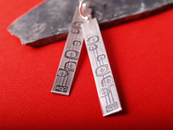 long rectangle sterling earrings etched with a midcentury modern abstract flower design on a slab of slate with a red background closeup shot
