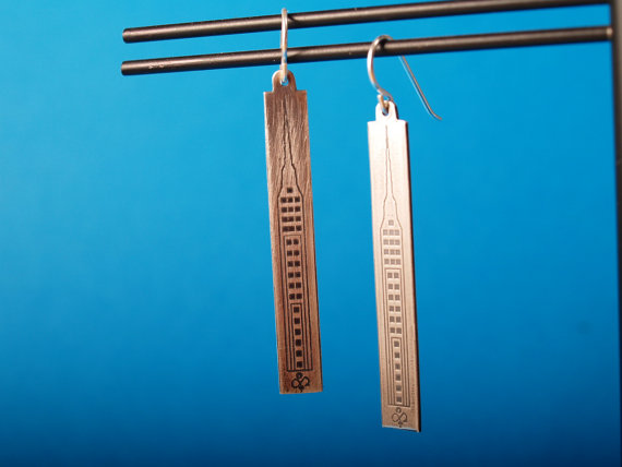 skyscraper earrings hanging on a stand against a blue background