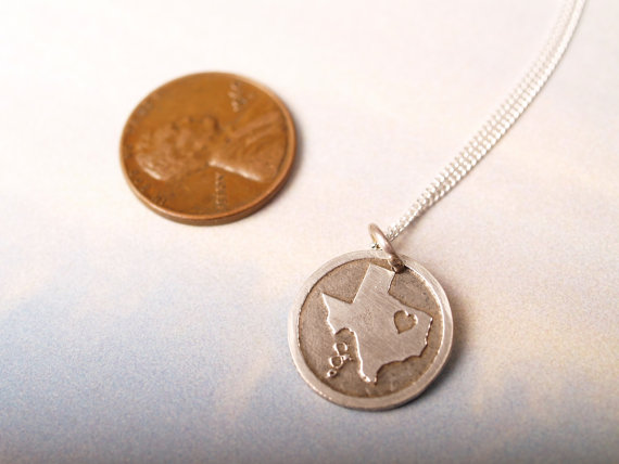 round etched sterling pendant featuring the state of Texas with a heart in northeast part of the state shown with a penny for scale