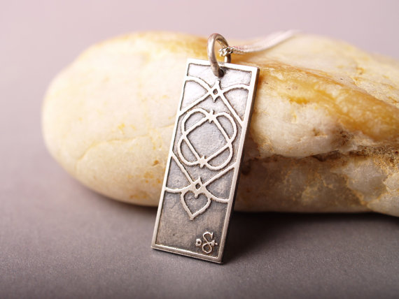 rectangular etched sterling silver pendant with overlapping hearts to create an ornate pattern shown leaned against pale stones grey background