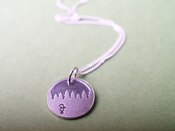round sterling etched pendant showing a forest treeline displayed on green field