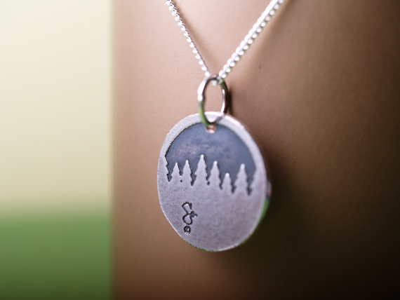 round sterling etched pendant showing a forest treeline displayed hanging on a copper card