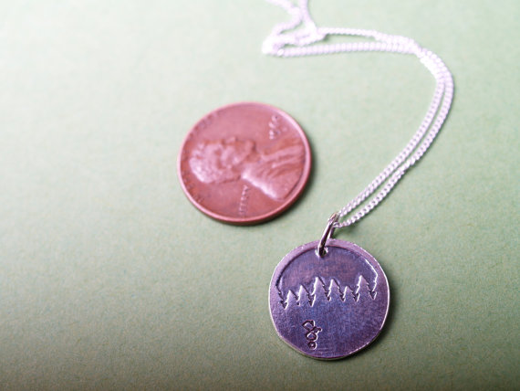 round sterling etched pendant showing a forest treeline displayed with a penny for scale
