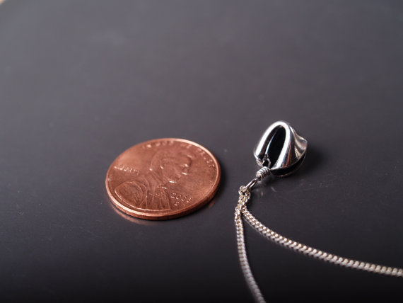 sterling fortune cookie pendant on chain shown on dark grey field with penny for scale