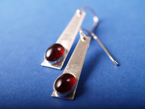 red oval garnet cabochons set in brushed sterling trapezoids with French hooks - shown on blue field