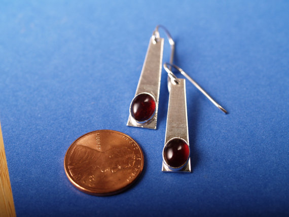 red oval garnet cabochons set in brushed sterling trapezoids with French hooks - shown on blue field with penny for scale