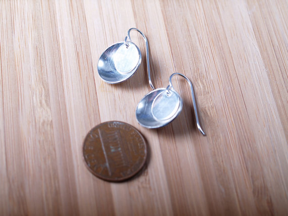 small round sterling earrings concave outside with lightly textured flat disk that hangs in the top on French hooks - shown with a penny for scale