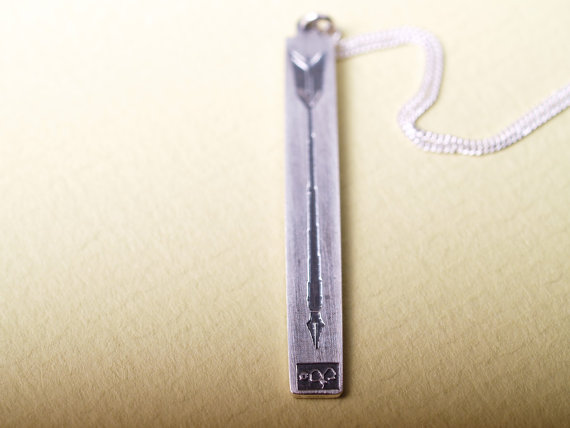 rectangular long etched sterling pendant featuring a long arrow with a calligraphy pen tip shown on a green field