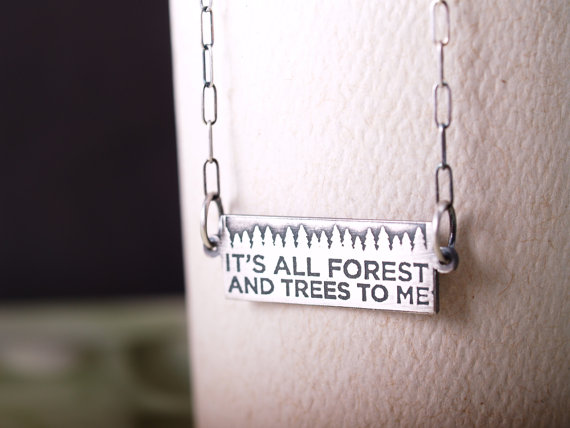 horizontal sterling etched pendant with chain on either sides featuring the motto It's all forest and Trees to me shown on a white card closeup