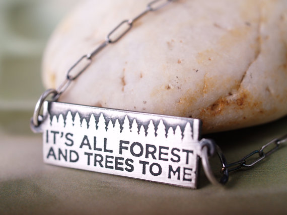 horizontal sterling etched pendant with chain on either sides featuring the motto It's all forest and Trees to me with a stone