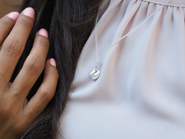 sterling silver fortune cookie pendant shown on model against a pale pink background