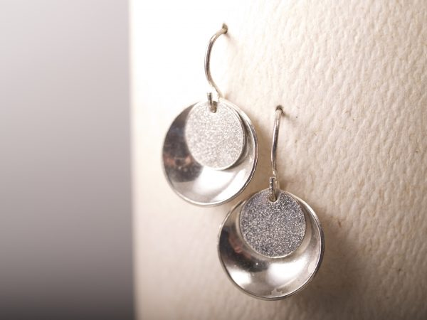 small round sterling earrings concave outside with lightly textured flat disk that hangs in the top on French hooks - shown on white card