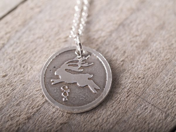 round sterling silver pendant etched with a jackalope design on a sterling chain shown against a grey barnwood background