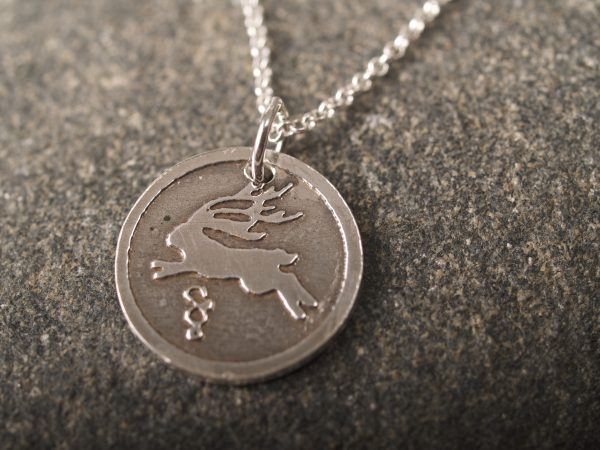 round sterling silver pendant etched with a jackalope design on a sterling chain shown against a dark grey granite background