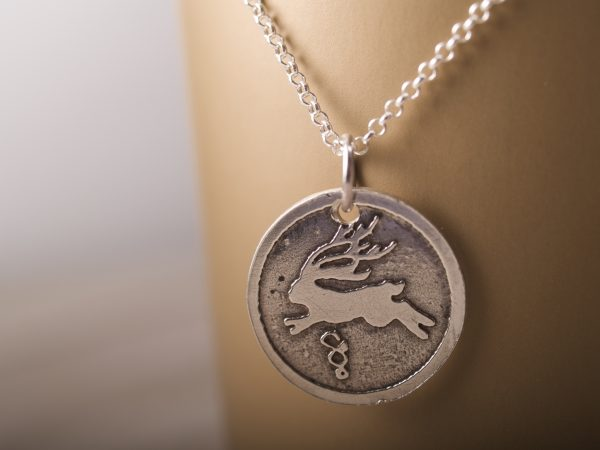 round sterling silver pendant etched with a jackalope design on a sterling chain shown hanging against a gold background