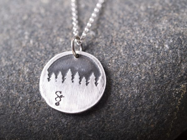 round sterling etched pendant showing a forest treeline on granite feature image