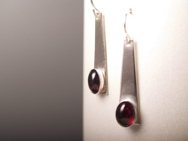 red oval garnet cabochons set in brushed sterling trapezoids with French hooks - shown hanging on white