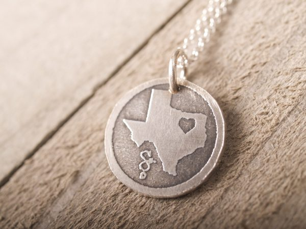 round etched sterling pendant featuring the state of Texas with a heart in northeast part of the state feature image on barnwood