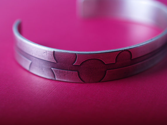 etched sterling silver cuff designed with a straight line and off set bubbles for an art deco design feature image on magenta