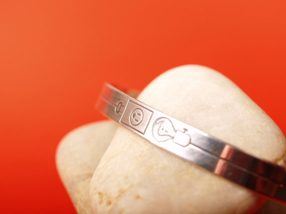 slim sterling cuff etched with a lightbulb and electrical outlet in the center closeup image center on stone
