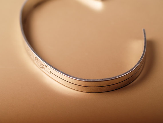 slim sterling cuff etched with a lightbulb and electrical outlet in the center side view to show thickness