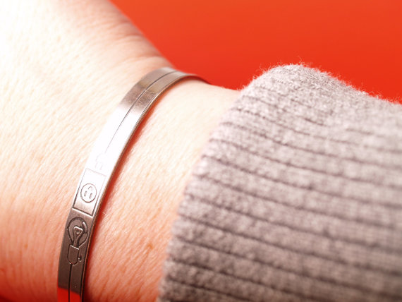 slim sterling cuff etched with a lightbulb and electrical outlet in the center image of cuff on wrist