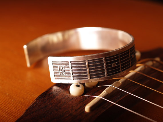 etched sterling cuff featuring fretboard pattern of a guitar pic of artist mark