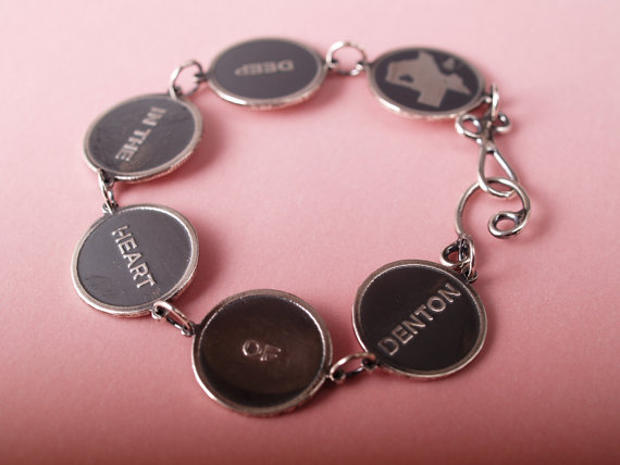 sterling disk bracelet reading shape of Texas Deep in the heart of Denton on a pale red field Denton end