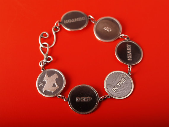 sterling disk bracelet reading shape of Texas Deep in the heart of Denton on a red field