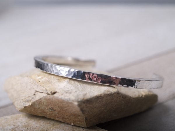 hammered sterling silver straight cuff shown lying on sandstone