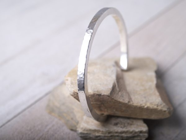 hammered sterling silver straight cuff shown on sandstone standing