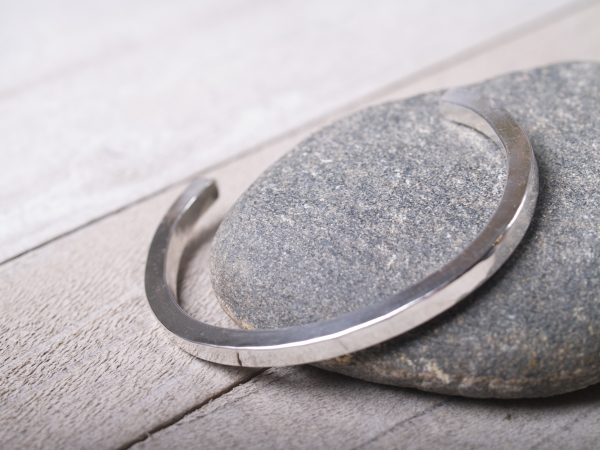 hammered sterling silver straight cuff shown lying on granite