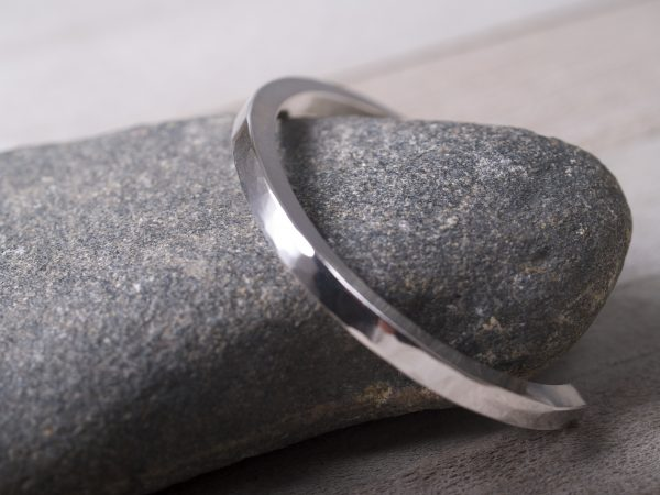 plannished sterling silver straight cuff shown on granite