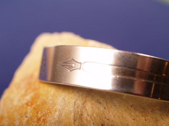 shiny sterling cuff with a pen nib on one end and the feathered end of an arrow on the other shown closeup on stone