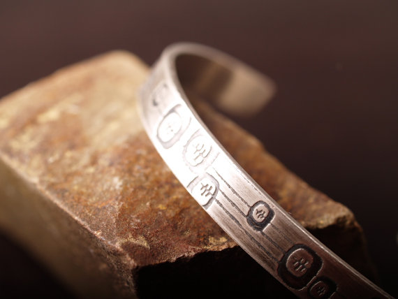 sterling etched cuff featuring an abstract floral design closeup shown on a stone